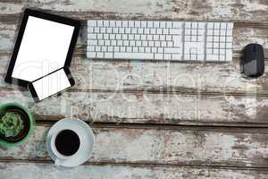 Digital tablet, smartphone, keyboard and mouse with coffee cup