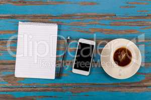 Notepad, pencil, smartphone and cup of tea