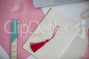 Diary, bookmark, ruler, ribbon and laptop