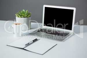Laptop with cup of coffee and diary