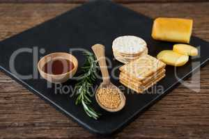 Cheese, crackers, nacho chips and rosemary herbs on slate plate