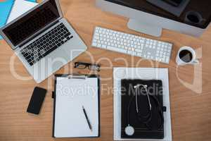 Computer, laptop, smart phone, clipboard, pen, spectacles, stethoscope and cup of coffee