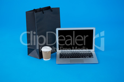 Shopping bag and disposable coffee cup with laptop
