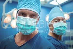 Portrait of male surgeons wearing surgical mask in operation theater