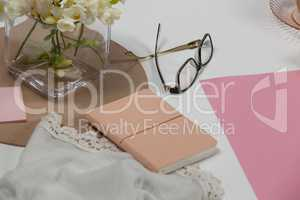 Spectacles, diary, cloth, blank page, paper balls and flowers
