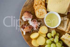 Variety of cheese with grapes, peach, meat and crackers