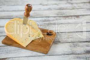 Knife on cheese slice on wooden board
