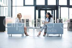 Businesswomen sitting in armchair and having a conversation