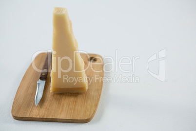 Piece of cheese with knife on cutting board