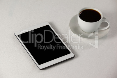 Digital tablet and cup of coffee