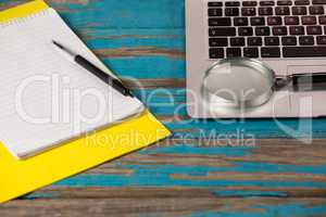 Laptop, magnifying glass, sticky notes, notepad and pen