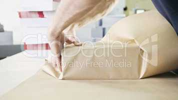Close up man's hands packing boxes of sellotape in printing industry