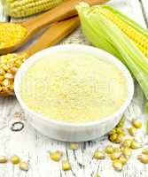 Flour corn in bowl with cobs on board