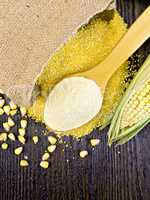 Flour corn in spoon with grains on board top