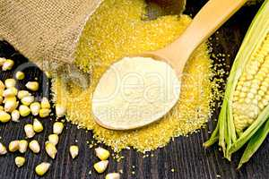 Flour corn in spoon with grains on dark board