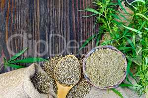 Flour hemp in bowl and corn in spoon on wooden board