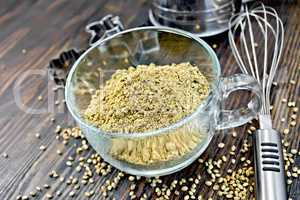 Flour hemp in glass cup with mixer on dark board