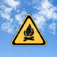 Glossy Fire danger sign on beautiful sky background.