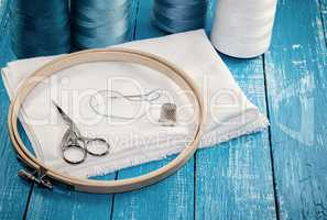 Threads in spools with white cloth for the embroidery and sewing