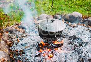 Metal pot over a campfire outdoors