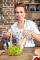Woman mixing fresh vegetable salad