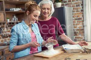 Grandmother and granddaughter sifting flour
