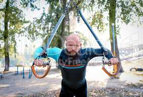 Young man training at outdoor gym