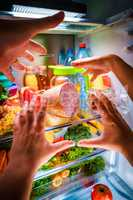 Human hands reaching for food at night in the open refrigerator