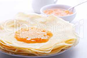 Crispy crepes with apricot jam served on a table.