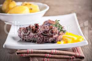Rabbit in winy sauce with potato on a white plate.