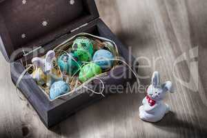 Easter bunny with colorful eggs in a box.