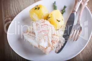 Steamed fish and potato on a plate served on plate.