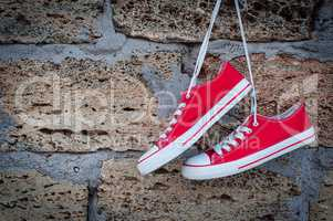 pair of red sneakers sport on the background wall with brickwork