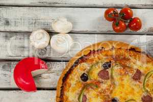 Italian pizza on wooden plank with vegetables and cheese