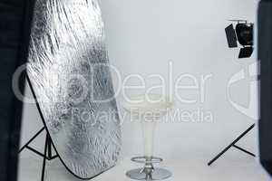 Stool with reflector and studio light in studio