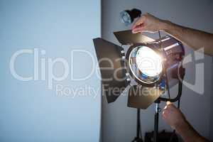 Photographer adjusting spotlight
