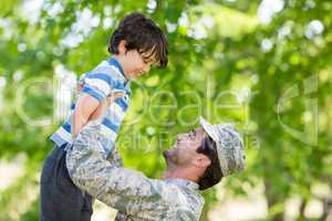 Army soldier lifting boy