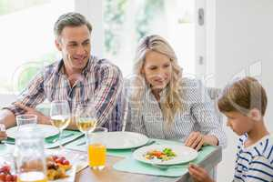 Parents interacting with son on dining table