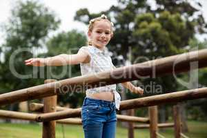 Girl playing on a playground ride in park