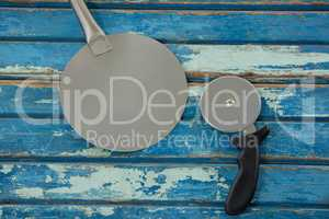 Spatula with pizza cutter on a wooden plank