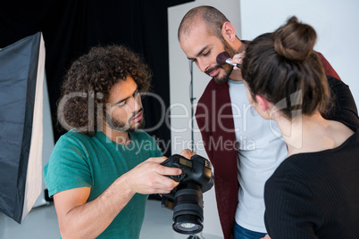 Model looking at photos in the camera while getting ready for a shoot