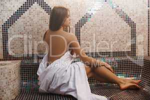 Topless girl wrapped in a bedsheet shot in sauna