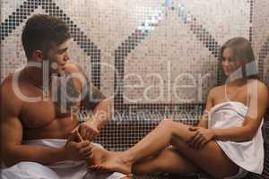 Young man making sexy girl foot massage in sauna