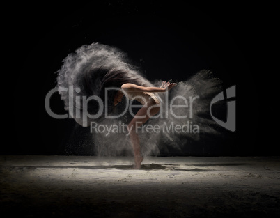 Dancer moving in cloud of white dust at studio