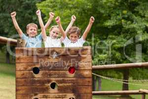 Kids standing with arms up on a playground ride in park