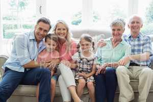 Multi generation family sitting on sofa in living room
