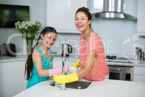 Mother assisting her daughter in cleaning vessel at home