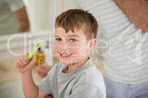Portrait of boy brushing teeth in bathroom