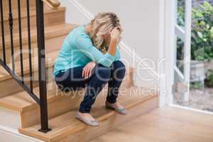 Tense woman sitting on staircase with hand on forehead