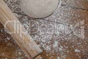 Rolling pin with pizza dough and flour on wooden plank
